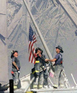 Firemen wih American Flag at Ground Zero